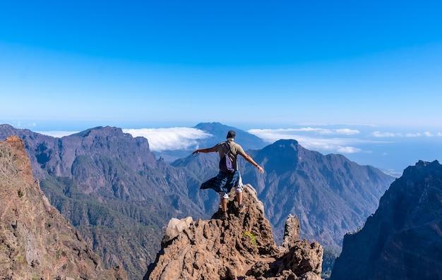 Een jonge man na het beëindigen van de tocht op de top van de vulkaan caldera de taburiente nabij roque de los muchachos op een zomermiddag, la palma, canarische eilanden. spanje