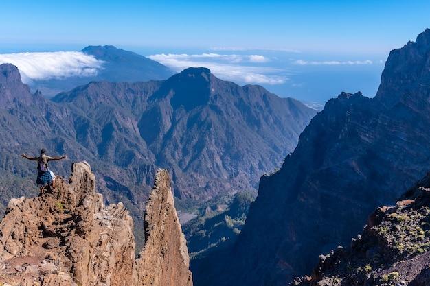 Een jonge man na het beëindigen van de trektocht op de top van de vulkaan caldera de taburiente nabij roque de los muchachos, kijkend naar het ongelooflijke landschap, la palma, canarische eilanden. spanje