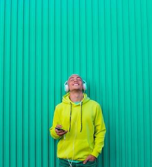 Een jonge man of tiener millennial die muziek luistert terwijl zijn telefoon en koptelefoon omhoog kijkt