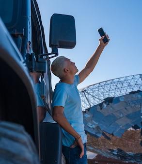 Een jonge man of tiener op zoek naar signaal met zijn telefoon en auto - millennial verslaafd aan telefoon in het nergens op zoek naar verbinding - blond haar volwassene