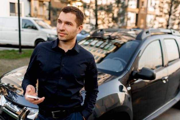 Een jonge man of zakenman in een donker overhemd staat op straat bij de auto, kijkt in de verte in een woonwijk van de stad. de chauffeur wacht op zijn passagier of klant.