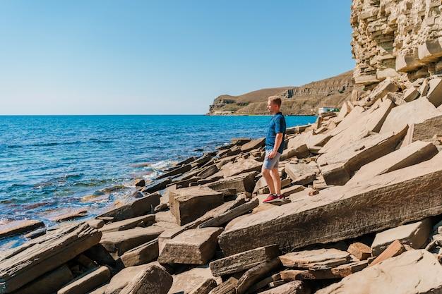 Een jonge man op een rotsachtig strand gemaakt van natuursteen op de krim
