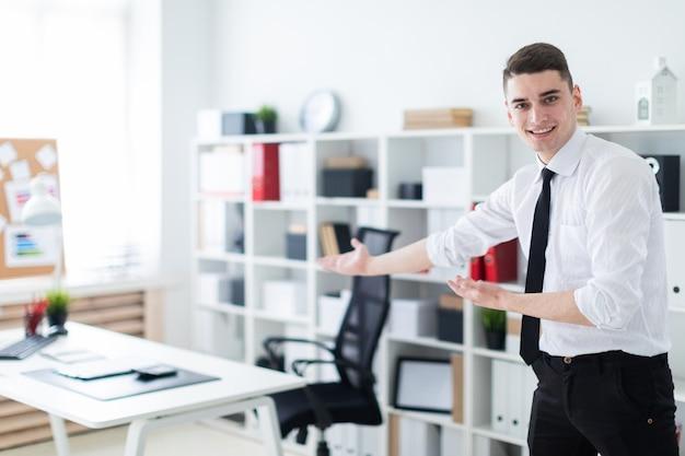 Een jonge man op kantoor nodigt je uit om aan tafel te gaan zitten.