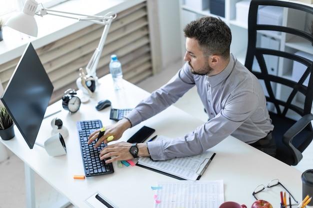 Een jonge man op kantoor zit aan een tafel, houdt een marker in zijn hand en werkt met documenten en een computer.