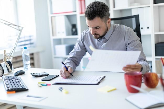 Een jonge man op kantoor zit aan een tafel, houdt een pen in zijn hand en werkt met documenten.