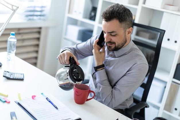 Een jonge man op kantoor zit aan een tafel, praat aan de telefoon en giet koffie in een kopje
