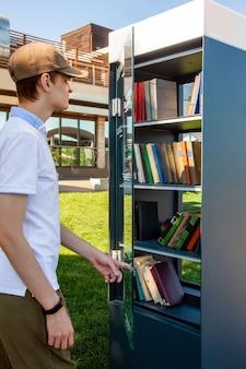 Een jonge man opent de glazen deur en haalt boeken uit een gratis boekenruilpunt
