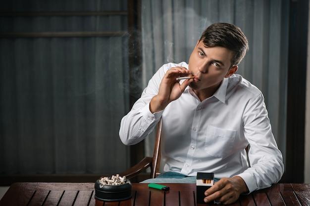 Een jonge man poseert zittend aan een tafel waarop een asbak vol sigaretten staat