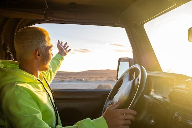 Een jonge man rijdt in zijn auto en kijkt naar de zonsondergang terwijl hij geniet van zijn vakanties en vakantie buiten alleen - reizen en reisconcept - tiener met auto die naar de zon kijkt