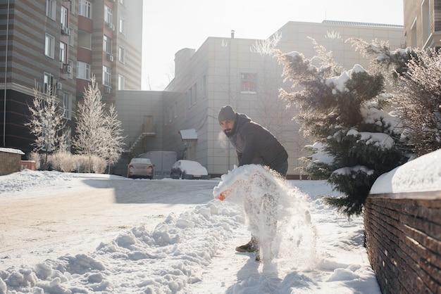 Een jonge man ruimt de sneeuw voor het huis op een zonnige en ijzige dag. de straat schoonmaken van sneeuw.