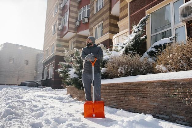 Een jonge man ruimt de sneeuw voor het huis op een zonnige en ijzige dag.