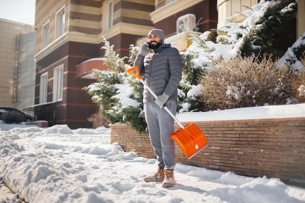 Een jonge man ruimt op een zonnige en ijzige dag de sneeuw voor het huis en praat aan de telefoon.