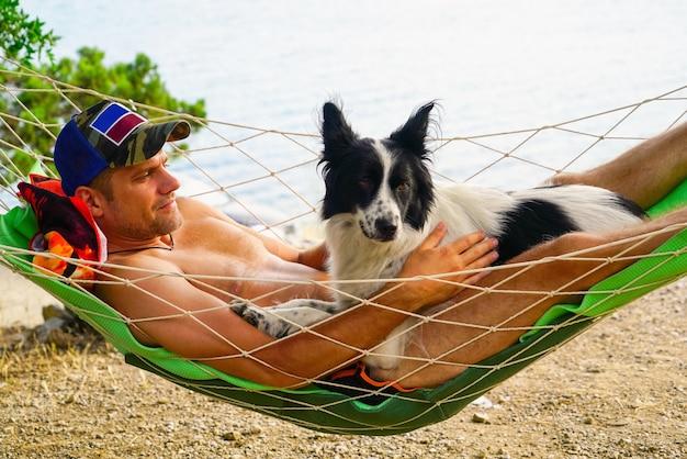 Een jonge man rust in een hangmat op het strand met een hond.