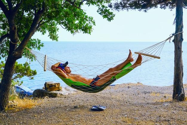 Een jonge man rust in een hangmat op het strand.