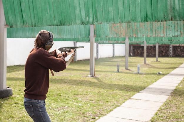 Een jonge man schiet op metalen vlaggen, doelen. vuurwapens pumpaction shotgun.