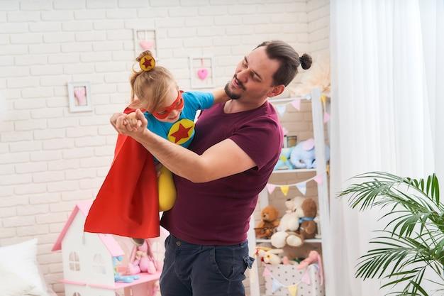 Een jonge man speelt met zijn dochter in superhelden in de kamer.