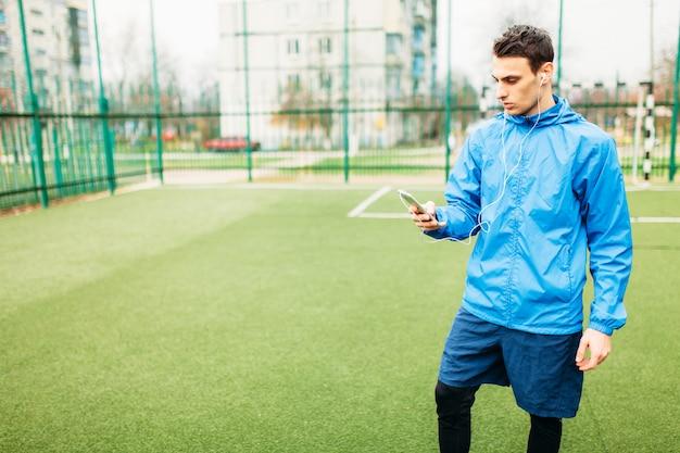 Een jonge man sport, rent op het voetbalveld. de man werkt in de open lucht.