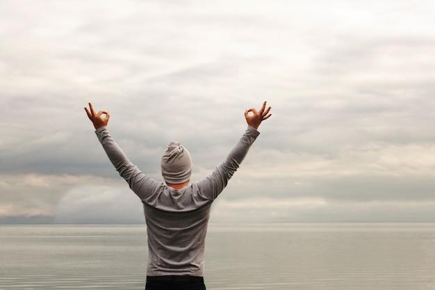 Een jonge man staat aan de kust. het uitzicht vanaf de achterkant. yoga lessen. handen omhoog. toont met handen ok teken. vrijheid en prestatie.