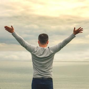 Een jonge man staat aan de kust. het uitzicht vanaf de achterkant. yogalessen. handen omhoog. vrijheid en prestatie.
