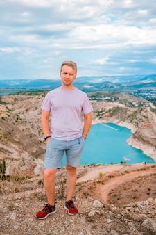 Een jonge man staat bij een steengroeve in de vorm van een hart met turkoois water op de krim
