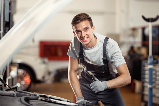 Een jonge man staat glimlachend naast een auto op zijn werk. onderhoud van auto's en voertuigen.