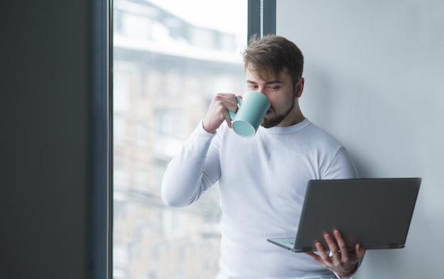 Een jonge man staat met een laptop bij het raam en drinkt koffie uit een kopje