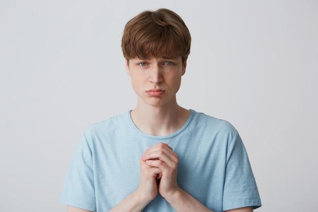Een jonge man staat met een smekende uitdrukking op zijn gezicht