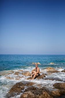 Een jonge man staat op de rotsen met uitzicht op de open middellandse zee. een man op een warme zonnige zomerdag kijkt naar de zeebries