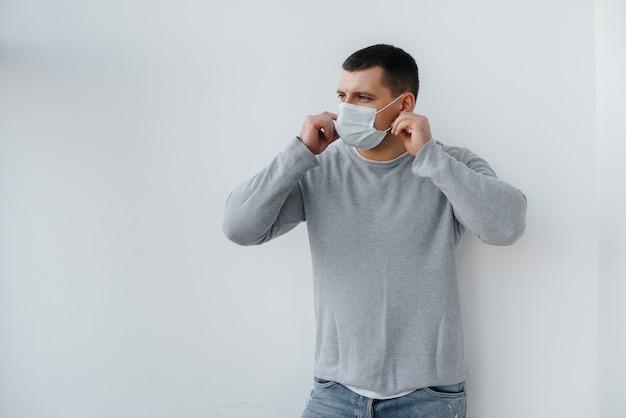 Een jonge man staat op een grijze ondergrond met een masker op tijdens een quarantaine met vrije ruimte