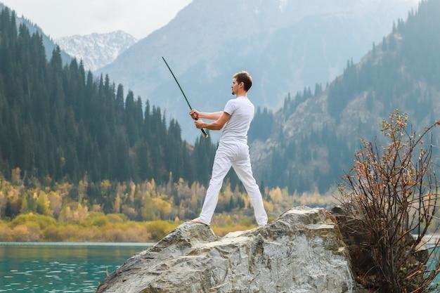 Een jonge man staat op een grote steen en houdt een japans zwaard in zijn handen.