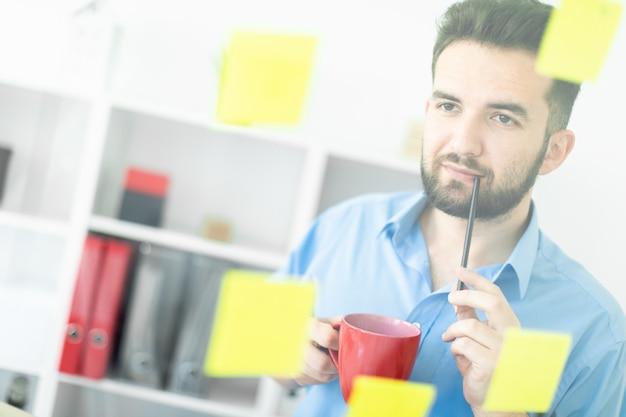 Een jonge man staat op kantoor bij een transparant bord met stickers.
