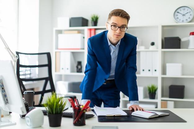 Een jonge man staat op kantoor, handen op de tafel.