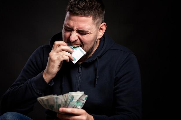 Een jonge man steekt geld in zijn mond.