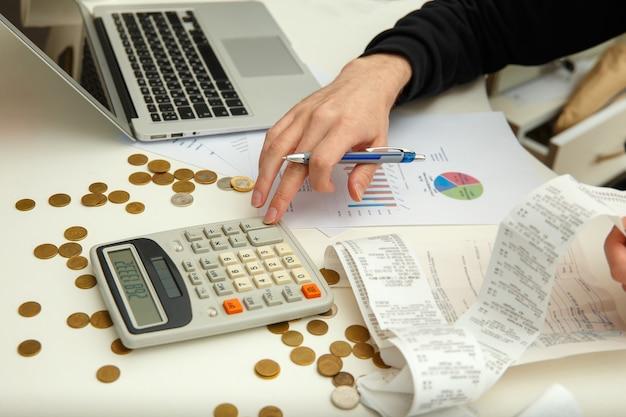 Een jonge man telt winsten en belastingen
