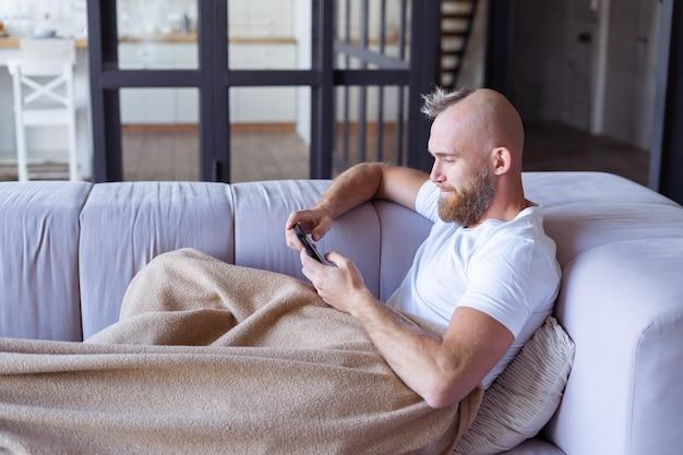 Een jonge man thuis op de bank komt naar buiten met een gezellige warme deken, houdt een mobiele telefoon vast, leest het nieuws, kijkt naar een video