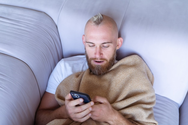 Een jonge man thuis op de bank komt naar buiten met een knusse warme deken, houdt een mobiele telefoon vast en leest het nieuws