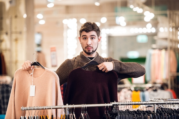 Een jonge man toont zijn vriendin de beschikbare kleuren van truien in het vrouwelijke warenhuis
