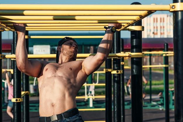 Een jonge man trekt zich omhoog op het sportveld, een atleet traint buiten in de stad