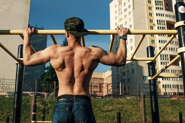 Een jonge man trekt zich omhoog sportveld, een atleet, buiten trainen in de stad