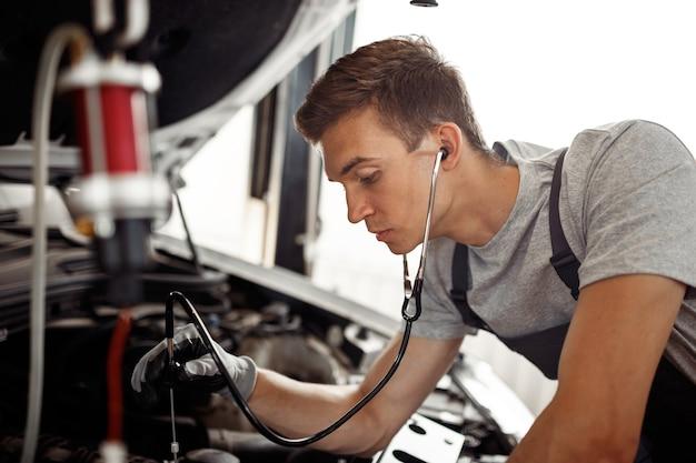 Een jonge man voert een gedetailleerd onderzoek uit van een automotor in een autowerkplaats