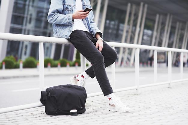 Een jonge man wacht op een passagier op de luchthaven.