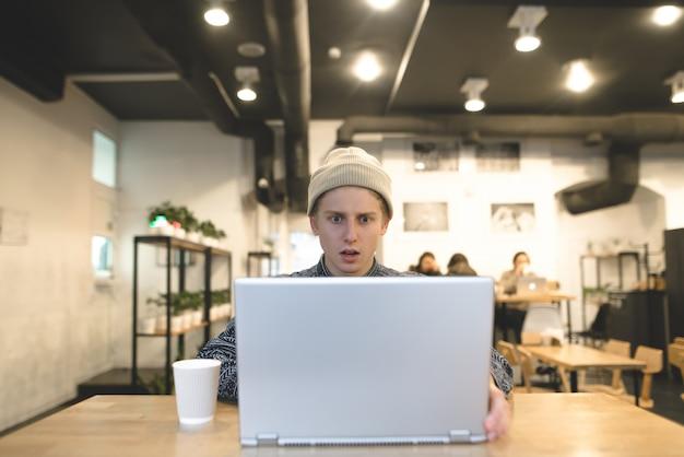 Een jonge man werkt in een café en kijkt verbaasd naar het laptopscherm. de student gebruikt internet in een gezellig café.