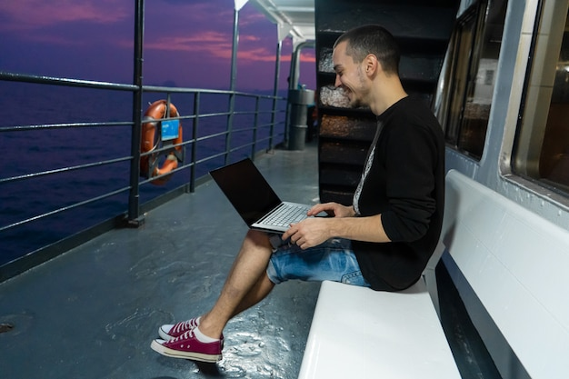 Een jonge man werkt op een laptop op het dek van een schip. afstandswerk. altijd in contact.