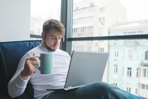 Een jonge man werkt op een sofa voor een laptop met een kop warme drank.