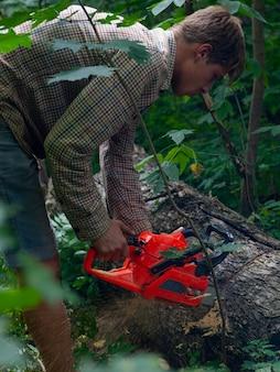 Een jonge man zaagt met een kettingzaag van boomstronken, verwijderde bosopstanden van oude bomen