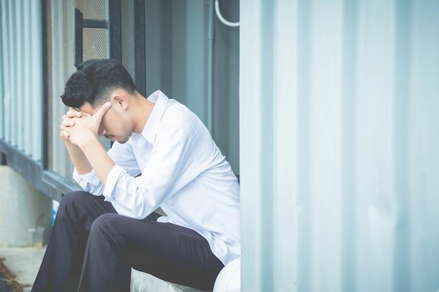 Een jonge man zat met zijn handen dicht bij zijn gezicht en had medelijden met wanhoop in het leven.
