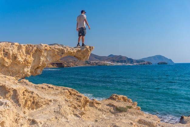 Een jonge man zat op de rotsen en keek naar playa los escullos in het natuurpark van cabo de gata, nijar, andalusië. spanje, middellandse zee