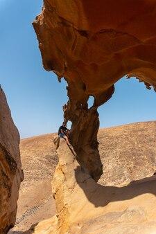 Een jonge man zit aan de mirador de la peñitas in de peñitas canyon, fuerteventura, canarische eilanden. spanje