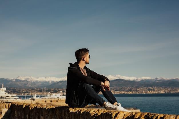 Een jonge man zit aan de waterkant en genietend van het uitzicht op zee.