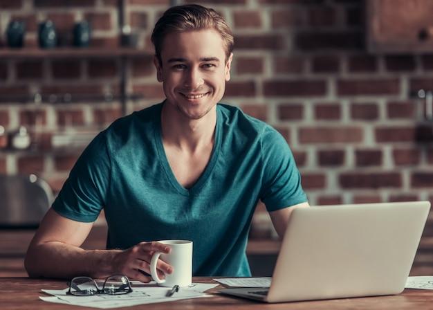 Een jonge man zit aan een tafel in het kantoor en werkt op een computer. brunette zit achter een computer en werkt met een kopje koffie in haar handen.